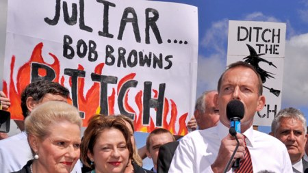 Tony Abbott standing in front of Julia bitch banner